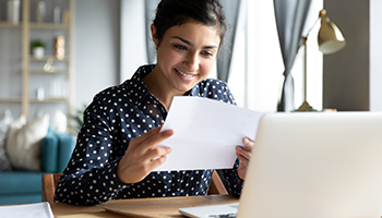Woman smiling at piece of paper in front of her laptop