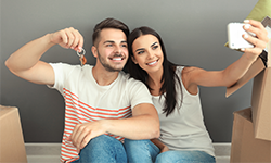 Couple sitting on floor of new house taking pictures surrounded by boxes