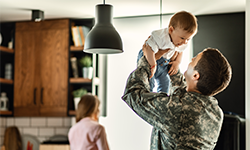 Man in camouflage raising baby in air with woman in background of kitchen