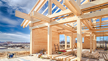 Wood studs of house being built with blue sky behind it