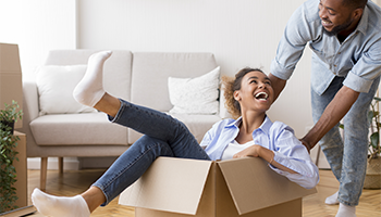 Man pushing woman in moving box in newly moved-in living room