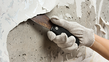 Person using scraping tool to take texture off of wall
