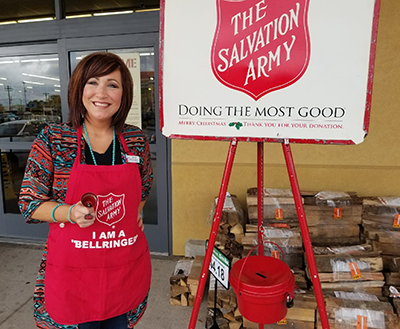 Woman ringing the Salvation Army bell outside of a grocery store entrance