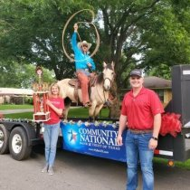 Person riding a horse on a float and person holding a trophy from the Freestone County Parade
