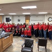 Corsicana employees wearing red shirts in support of Monica Aldama's Dancing With the Stars competition
