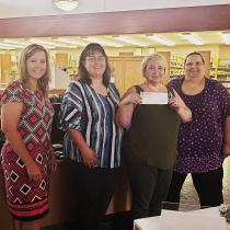 Women standing together holding check