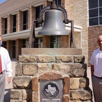 Men standing beside bell