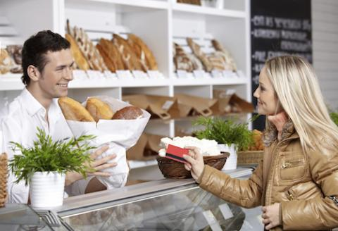 Woman handing a store worker a credit card