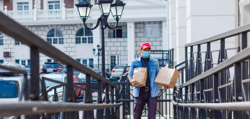 man with mask carrying bags up walkway