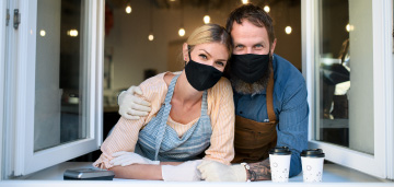 couple with masks leaning out window