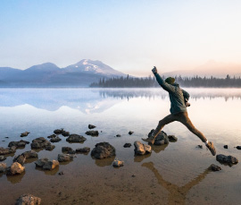 person jumping on rocks