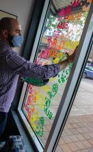 Verity staff painting Greenwood's window